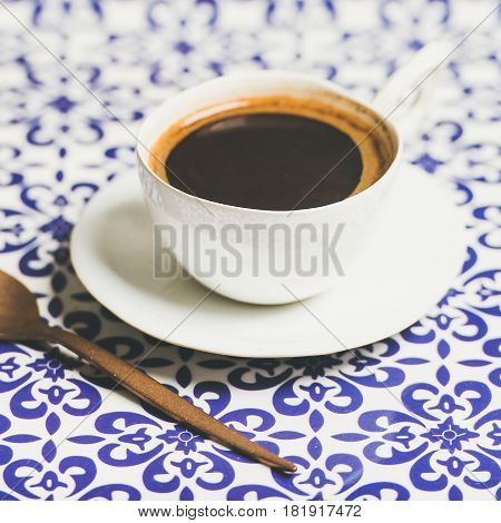 Cup of black Turkish or Eastern style coffee over oriental bright motley Moroccan patterned background, selective focus
