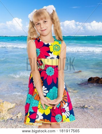 Beautiful little girl with long blonde ponytails on her head tied with white bows, bright summer dress and knee socks.On the background of sea beach, warm sea and blue sky with clouds.