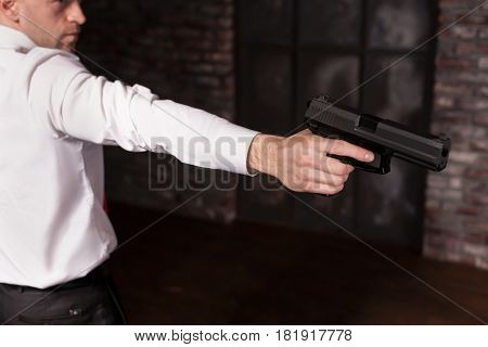 Serious hired murderer in red tie aims a gun