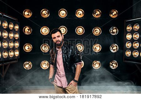 Bearded singer on stage with decorations of lights