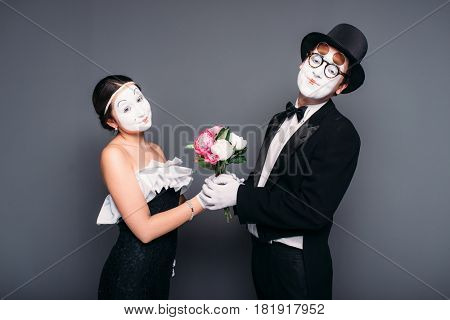 Pantomime actors performing with flower bouquet