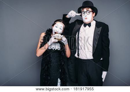 Mime actors performing, actress nibble alarm clock