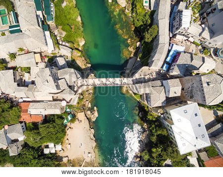 Aerial view of people crossing Old Bridge over Neretva river in Mostar, Bosnia and Herzegovina.