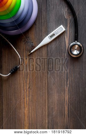 Child health care with stethoscope and thermometer in doctors office wooden desk background top view mock up