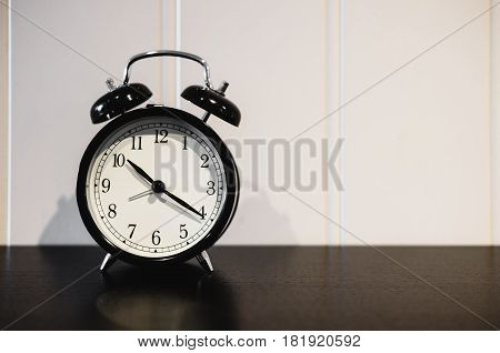 Alarm clock with 10 O'clock and twenty minuet, on black wooden table with white wall