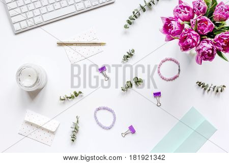 Trendy spring design of office workdesk with blossom on white background top view