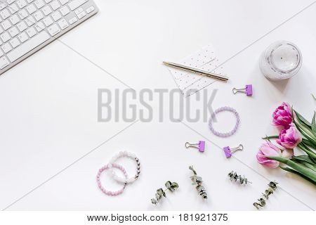 Spring pink flowers on workdesk at home ofiice white background top view mockup