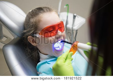close up view of small girl patient at the dentist. Doctor is making dental fillings with ultraviolet light. Girl is wearing protective glasses