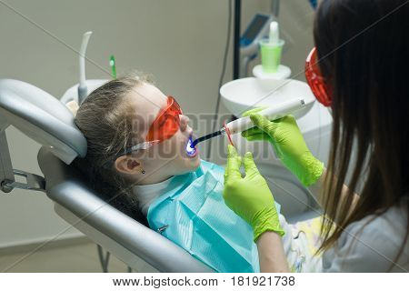 close up view of small girl patient at the dentist. Doctor is making dental fillings with ultraviolet light. Girl is wearing protective glasses.