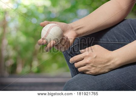 Hand holding a baseball on nature background