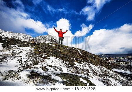 Traveler at mountains against beautiful blue sky staying in ancient stones.