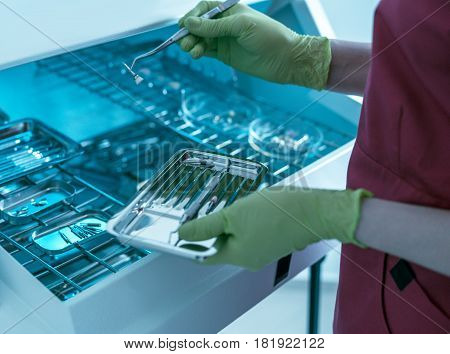 Close-up view of dentist hands with gloves holding dental instruments and consumable materials. Doctor is preparing for working with teeth. Different dental equipment