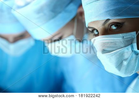 Three surgeons at work operating in surgical theatre. Resuscitation medicine team wearing protective masks saving patient. Surgery and emergency concept. Female surgeon portrait looking in camera