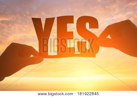 silhouette of hands holding yes word with sunshine
