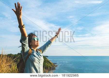 Happy Young Traveler Woman Raised Arm Up To Sky Enjoying A Beautiful Of Nature At Top Of Mountain An