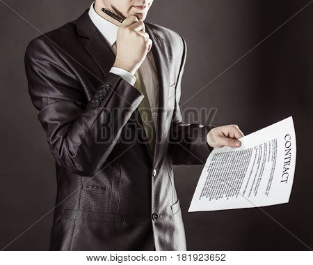 businessman holding a pen and a document with the terms of the contract.photo on a black background and has space for your text