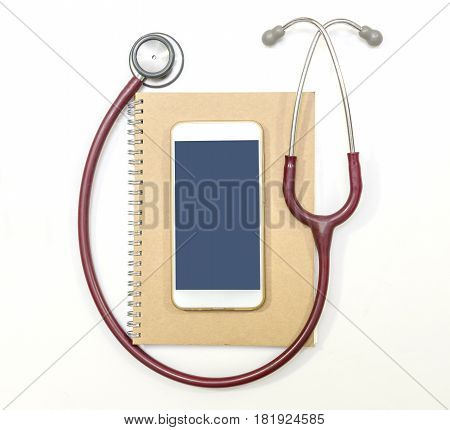 Top view of stethoscope mobile phone and brown notebook on white background flat lay.