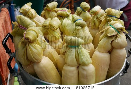 boiled corn with the leafy stalk  Boiled, ready to eat corn is sold in the sidewalks of Asian countries like Thailand, Philippines, and other countries.