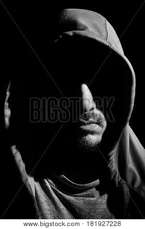 Portrait of a hooded man with his face wrapped in shadows.