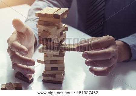 business man placing wooden block on a tower concept risk control Planning and strategy in business.vintage tone