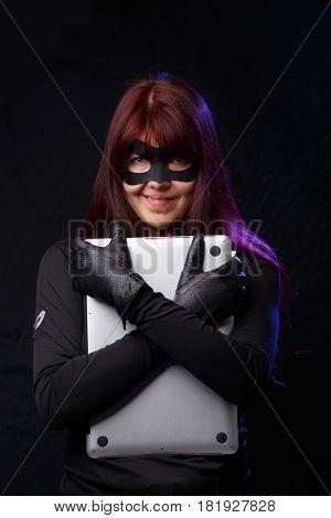 Woman hacker cuddles stolen laptop