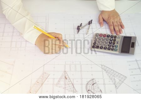 Close up Architect working on blueprint. Architects workplace architectural working of Architect sketching a construction project on his plane project. Construction concept