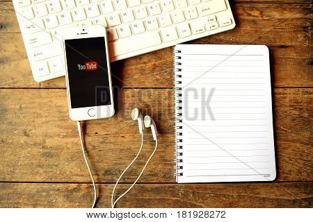 CHIANGMAI THAILAND -April 14 2016:Brand new Apple iPhone with YouTube app on the screen lying on desk with headphones.