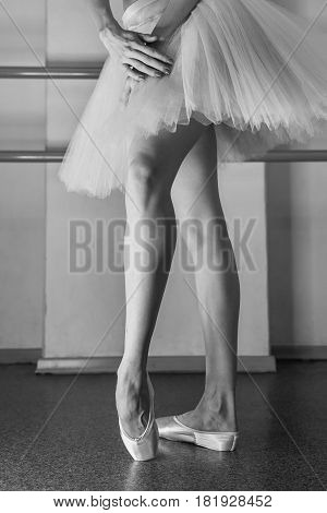 Ballerina in pointes and a pack warms up before the dance lesson. Long slender female feet. Classical ballet. Prima ballerina.