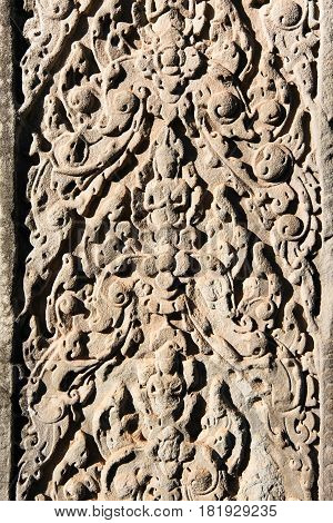 Detail close-up of the textured pattern of a carving in relief on stone wall at the Angkor Wat temple complex in Cambodia.