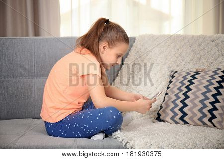 Incorrect posture concept. Cute schoolgirl with phone sitting on sofa