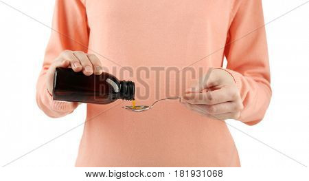 Woman pouring cough medicine syrup into spoon on white background