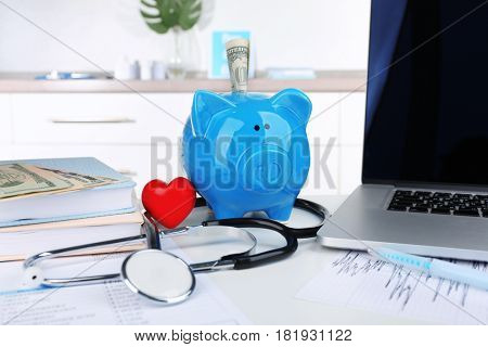 Piggy bank with little red heart and stethoscope on table