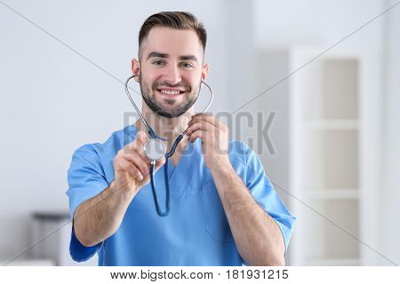 Young medical assistant with stethoscope in office