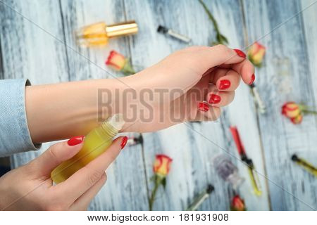 Female hands with bottle of perfume on wooden background, close up