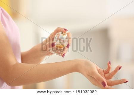 Beautiful young woman with bottle of perfume on blurred background, closeup