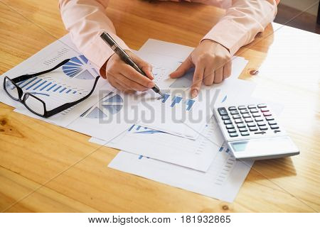 Business Woman Hand Pointing At Business Document During Discussion At Meeting And  Using A Calculat