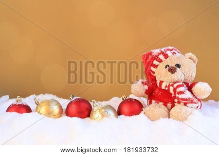 Teddybear sitting beside a row of Christmas ornaments.