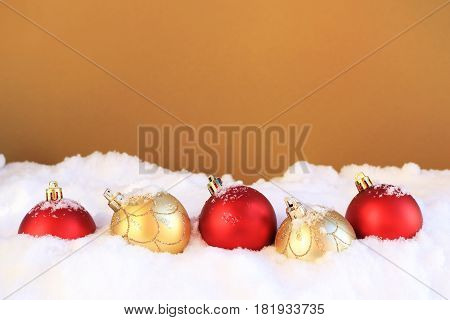 Row of red and gold Christmas ornaments in the snow.