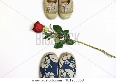 Red rose placed between two pairs of sneakers.
