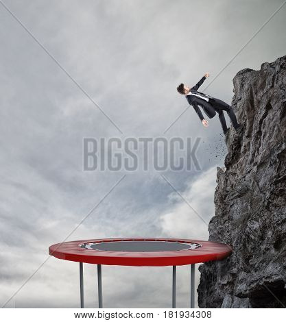 Businessman jumping on a trampoline to reach the flag at the top of the mountain. Achievement business goal and Difficult career concept