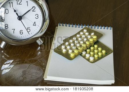 Close Up Of Contraceptive Pills And Clock On Wooden Background