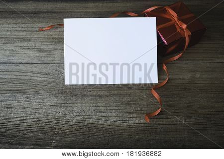 Gift Box With A Blank White Card, Presents And Christmas Letters All Around, Desktop Top View