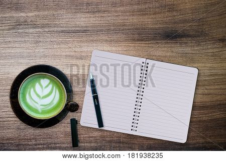 green tea latte whit notebook,pen on wood background