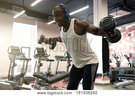 hard workout. Muscular black man doing exercises with dumbbells for back at gym