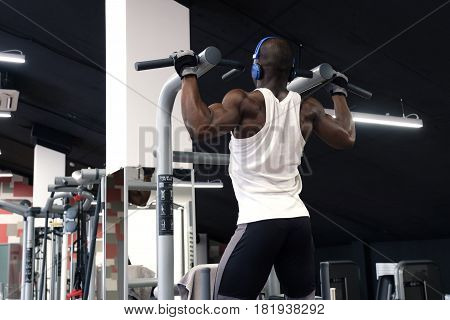 back view of a black man wearing white t-shirt doing exercises pull ups