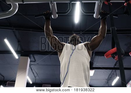 front view of a black man wearing white t-shirt doing exercises pull ups