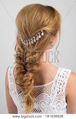 Hairstyle. Collected in a braid blonde hair with a beautiful decoration. Photo from the back on a light background