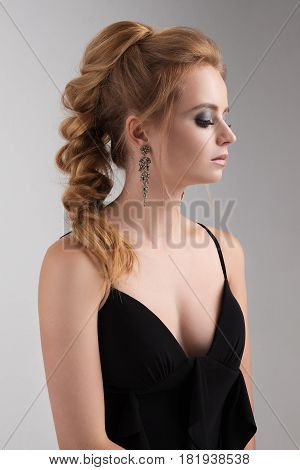 Portrait of a blonde with evening make-up and a highly assembled scythe in a black dress with a neckline. Vertical photo in profile on a light background