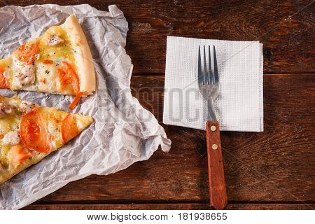 Two slices of homemade fresh yummy pizza with tomato, chicken and cheese served for lunch on white napkin with fork, on dark wooden rustic table, close up.