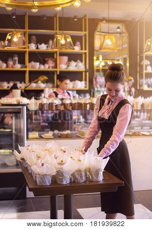 Pretty young girl serving easter cakes at the coffee shop. Waitress takes order communicates with clients against background of bar with variety of sweet stuff. Town Taganrog, Russia, April 14, 2017.